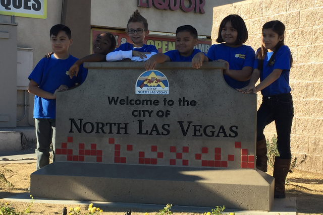Tom Williams Elementary School students gather around a new Welcome to Friendly North Las Vegas sign on the northwest corner of Pecos Road and Owens Avenue on Tuesday, Nov. 29, 2016. (City of Nort ...