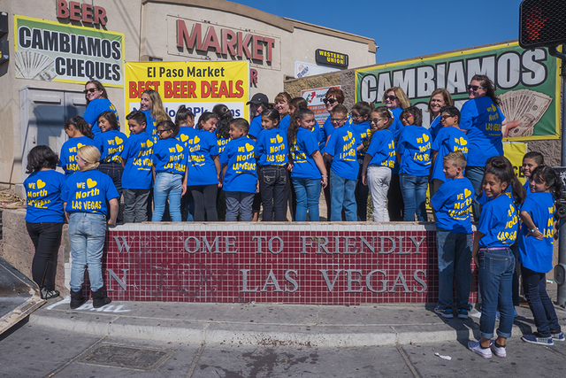 Tom Williams Elementary School students gather around an old Welcome to Friendly North Las Vegas sign on the northwest corner of Pecos Road and Owens Avenue. A new sign was unveiled on on Tuesday, ...