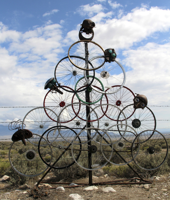 "Artist Joyce Nickerson created her sculpture ""Wheeler Peek"" out of old bicycle wheels and seats decorated with faces. She was forced to remove the work from the side of state Rou ..."