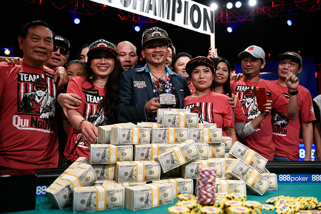 Qui Nguyen of Las Vegas, surrounded by family and friends, stands with a pile of cash and his championship bracelet after eliminating Gordon Vayo at the final table at the 2016 World Series of Pok ...