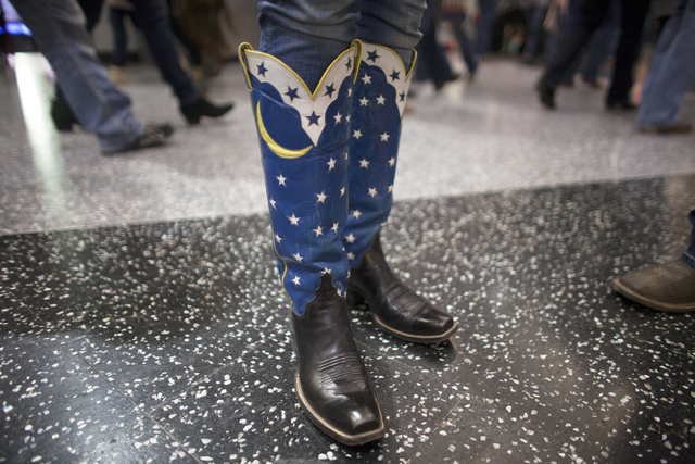 Beth Mathis shows off her cowboy boots at the National Finals Rodeo at Thomas & Mack Center ...