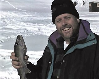 Chris Nielsen, the author's brother, shows off a plump rainbow trout caught while ice fishing at Panguitch Lake near Cedar City, Utah. The fish took rainbow colored PowerBait. Photo by Doug Nielsen.