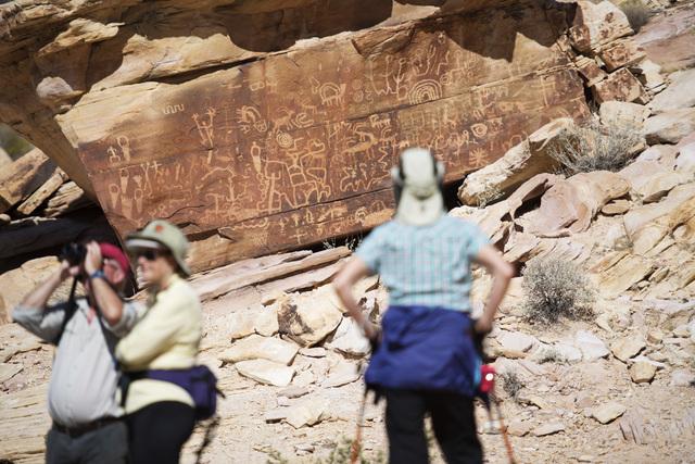 "Hikers check out ""Newspaper Rock"" in the Falling Man petroglyph area in the Gold Butte region Saturday, Oct. 15, 2016, northeast of Las Vegas. (Sam Morris/Las Vegas News Bureau)"