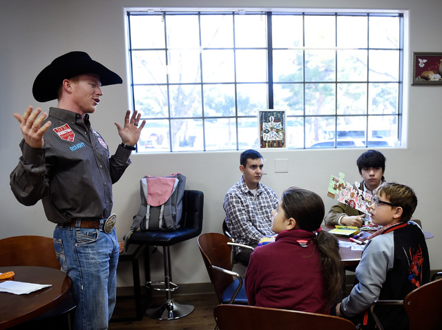 Saddle bronc world champion Jacobs Crawley, left, speaks with children during a visit to Grant a Gift Autism Foundation at the UNLV Medicine Ackerman Autism Center Friday, Dec. 2, 2016, in Las Veg ...