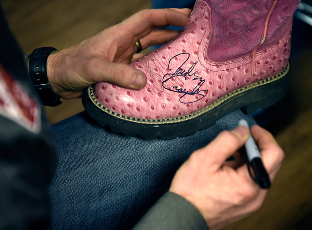 Saddle bronc world champion Jacobs Crawley signs an autograph on a boot during a visit to Grant a Gift Autism Foundation at the UNLV Medicine Ackerman Autism Center Friday, Dec. 2, 2016, in Las Ve ...