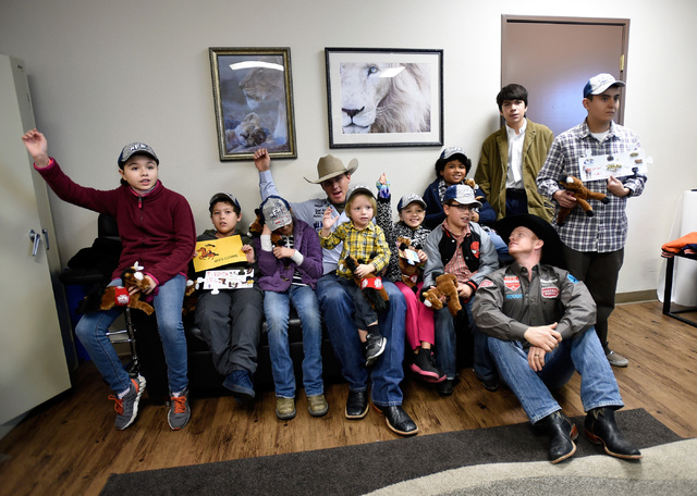 Tie-down roping world champion Caleb Smidt, fourth left, saddle bronc world champion Jacobs Crawley, third right, pose with children during a visit to Grant a Gift Autism Foundation at the UNLV Me ...