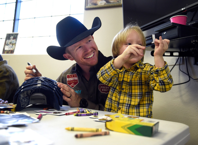 Saddle bronc world champion Jacobs Crawley, left, sits with Tristan Duenez, 3, during a visit to the Grant a Gift Autism Foundation at the UNLV Medicine Ackerman Autism Center Friday, Dec. 2, 2016 ...