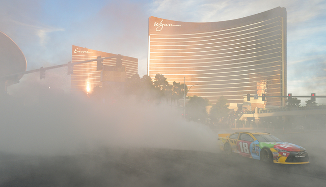 NASCAR's Kyle Busch emerges from a cloud of smoke in his No. 18 Toyota Camry for Joe Gibbs Racing in NASCAR Champions Week Victory Lap on the Las Vegas Strip at the intersection of Spring Mountain ...