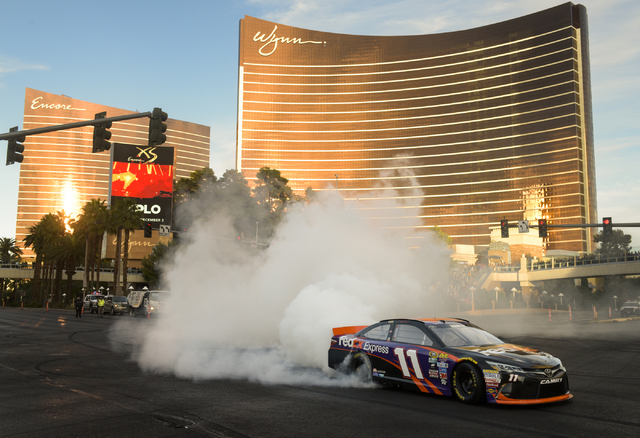 NASCAR's Denny Hamlin performs a burnout in his No. 11 FedEx Toyota Camry for Joe Gibbs Racing in NASCAR Champions Week Victory Lap on the Las Vegas Strip at the intersection of Spring Mountain Ro ...