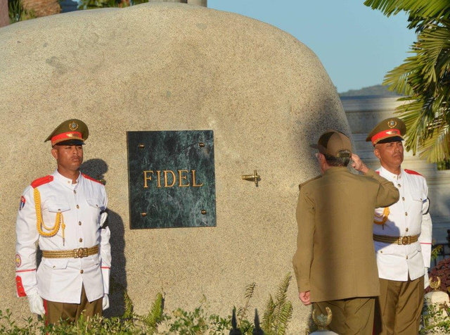 Cuba's President Raul Castro (C) salutes after placing the box containing the ashes of Cuba's former President Fidel Castro into a boulder at the Santa Ifigenia Cemetery, in Santiago de Cuba, Dece ...