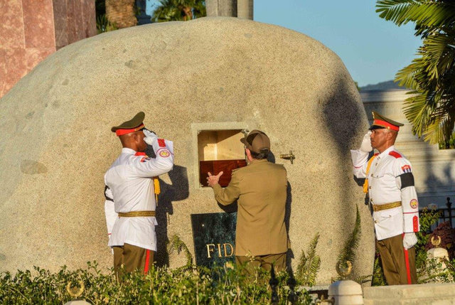 Cuba's President Raul Castro (C) places the box containing the ashes of Cuba's former President Fidel Castro into a boulder at the Santa Ifigenia Cemetery, in Santiago de Cuba, December 4, 2016. ( ...
