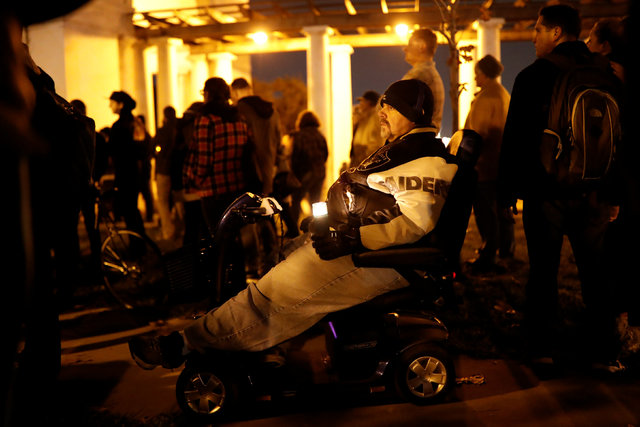 A man in a wheelchair holds a candle during a vigil for the victims of the fatal warehouse fire in Oakland, California, U.S. December 5, 2016. REUTERS/Stephen Lam