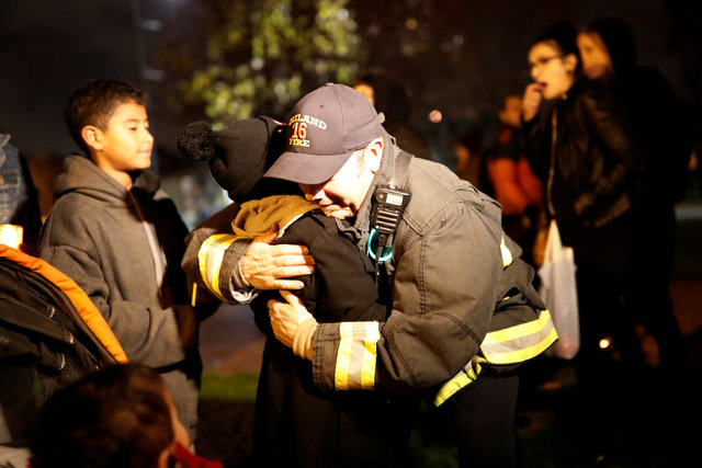A firefighter embraces a child during a vigil for the victims of the fatal warehouse fire in Oakland, California, U.S. December 5, 2016. REUTERS/Stephen Lam