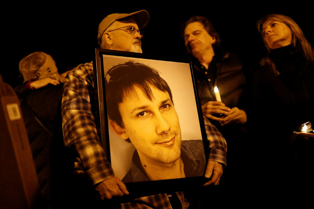 Brian Hough holds a photograph of his son Travis, who was among the deceased at the warehouse fire, during a vigil in Oakland, California, U.S. December 5, 2016. REUTERS/Stephen Lam
