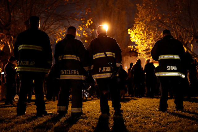 A group of firefighters stand amongst the crowd during a vigil for the victims of the fatal warehouse fire in Oakland, California, U.S. December 5, 2016. REUTERS/Stephen Lam