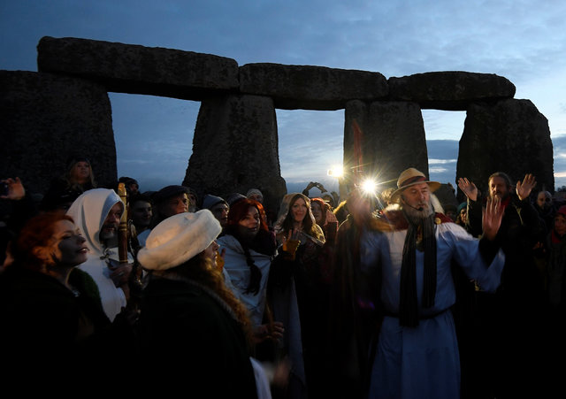 Visitors and revellers react amongst the prehistoric stones of the Stonehenge monument at dawn on Winter Solstice, the shortest day of the year, near Amesbury in south west Britain, December 21, 2 ...