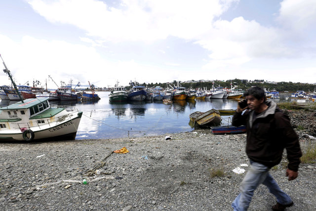 A man walks on a fishing bay during a tsunami alert at Calbuco town after a quake hit Chiloe island, southern Chile, December 25, 2016. REUTERS/Nicolas Klein