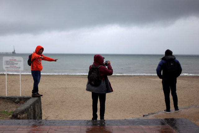 Locals are seen in front of an evacuated beach in Penco town during a tsunami alert after a quake hit Chiloe island, southern Chile, December 25, 2016. REUTERS/Juan Gonzalez EDITORIAL USE ONLY. NO ...
