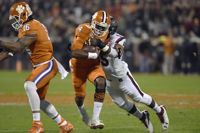 Clemson quarterback Deshaun Watson rushes, with blocking help from Jordan Leggett (16), while defended by South Carolina's Dante Sawyer during the first half of an NCAA college football game Satur ...