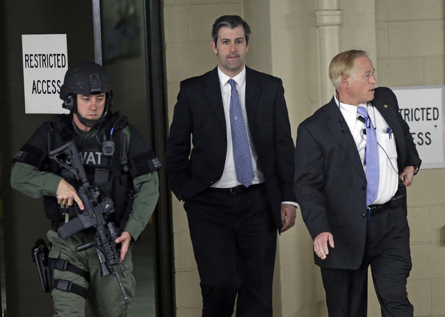 Former North Charleston police officer Michael Slager, center, is escorted from the courthouse during his murder trial at the Charleston County court in Charleston, S.C., Friday, Dec. 2, 2016. (Ch ...