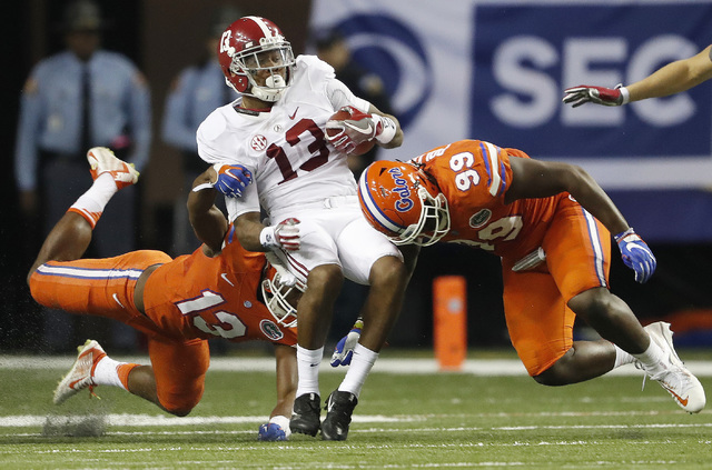 Alabama wide receiver ArDarius Stewart (13) is hit by Florida defensive lineman Jachai Polite (99) and Florida linebacker Daniel McMillian (13) during the second half of the Southeastern Conferenc ...