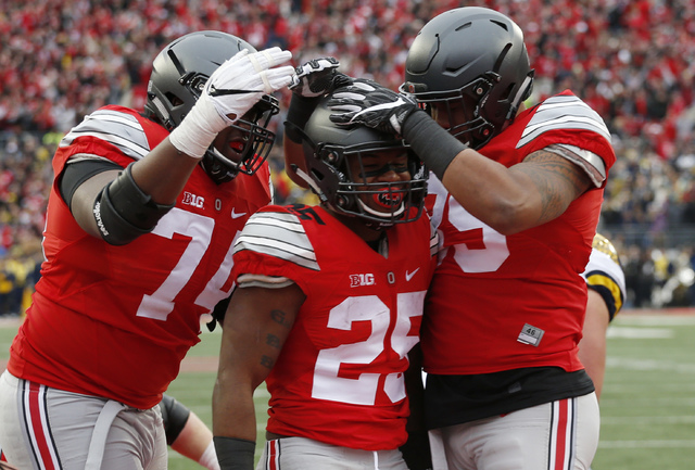 In this Nov. 26, 2016, file photo, Ohio State running back Mike Weber, center, celebrates his touchdown against Michigan with teammates Jamarco Jones, left, and Luke Farrell during the second half ...