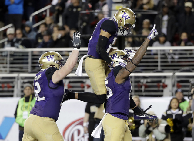 In this Friday, Dec. 2, 2016, file photo, Washington tight end Darrell Daniels, right, celebrates his touchdown catch with teammates Aaron Fuller, center, and Jake Eldrenkamp during the first half ...