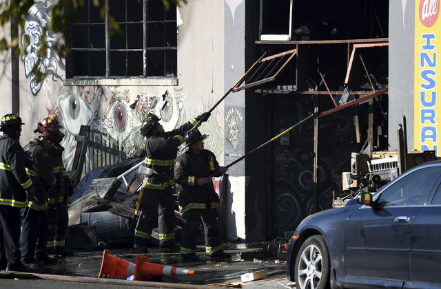 Firefighters clear an entry to a smoldering building after a fire tore through a warehouse party early Saturday, Dec. 3, 2016 in Oakland.   Oakland fire chief Teresa Deloche-Reed said many people  ...