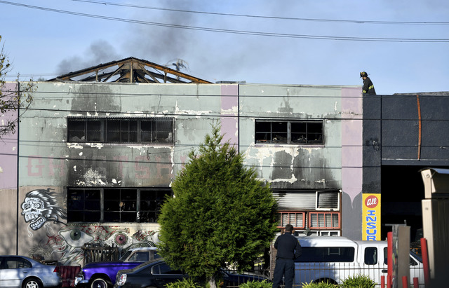 A firefighters walks on the roof of a smoldering building after a fire tore through a warehouse party early Saturday, Dec. 3, 2016 in Oakland.   Oakland fire chief Teresa Deloche-Reed said many pe ...