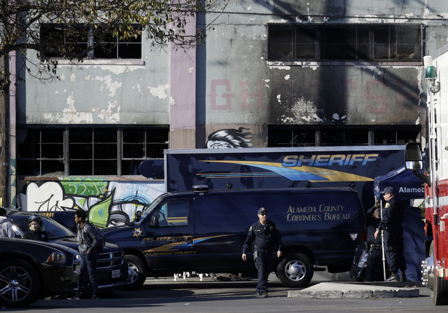 A coroner's van is parked outside of a warehouse after it was destroyed by a fire Saturday, Dec. 3, 2016, in Oakland, Calif.  Oakland fire chief Teresa Deloche-Reed said many people were unaccount ...