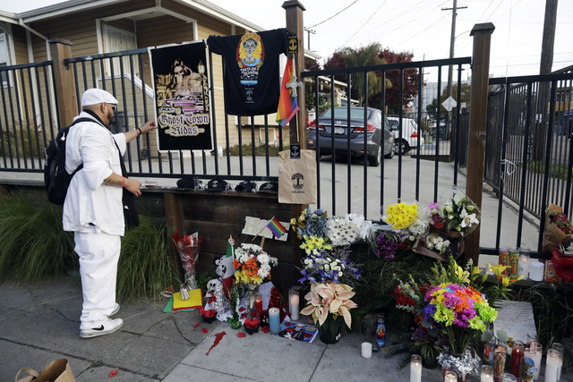 A man places additions to a makeshift memorial for victims of a warehouse fire near the site, Monday, Dec. 5, 2016, in Oakland, Calif. (Marcio Jose Sanchez/AP)