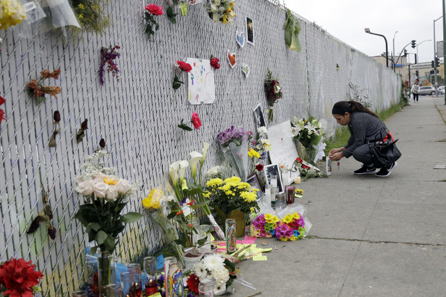 A woman lights a candle at a makeshift memorial near the site of a warehouse fire Monday, Dec. 5, 2016, in Oakland, Calif. (Marcio Jose Sanchez/AP)