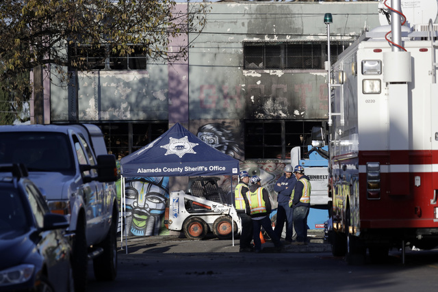 Crews stand outside the site of a warehouse fire, Sunday, Dec. 4, 2016, in Oakland, Calif. Officials said they are continuing to search the charred debris from the fatal fire that ripped through a ...