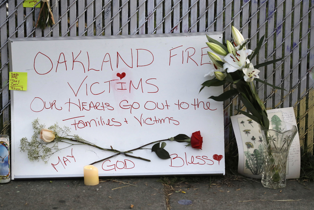 Signs and flowers adorn a fence near the site of a warehouse fire Monday, Dec. 5, 2016, in Oakland, Calif. The death toll in the Oakland warehouse fire on Friday climbed Monday with more bodies st ...