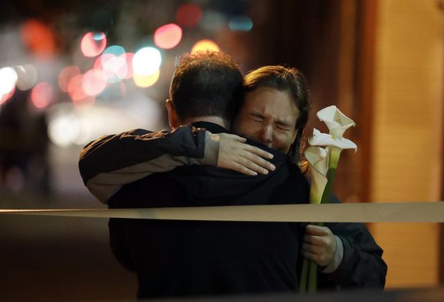 Mourners embrace near the site of a warehouse fire Sunday, Dec. 4, 2016, in Oakland, Calif. (Marcio Jose Sanchez/AP)