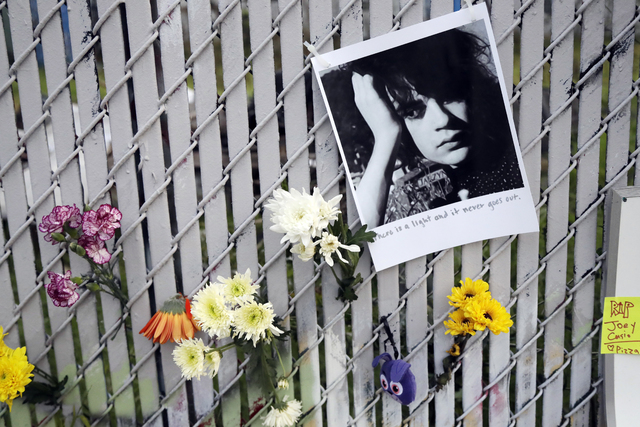 Pictures and flowers adorn a fence near the site of a warehouse fire Monday, Dec. 5, 2016, in Oakland, Calif. The death toll in the Oakland warehouse fire climbed Monday with more bodies still fea ...
