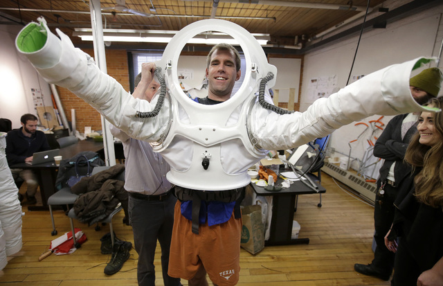 Andrzej Stewart, the chief engineering officer on a year-long Mars simulation mission that ended in August, puts on a new space suit at the Rhode Island School of Design in Providence, R.I. RISD c ...