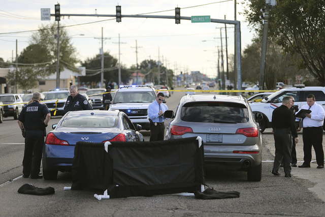 The body of former NFL player Joe McKnight lies between the shooter's vehicle at left and his Audi SUV at right as the Jefferson Parish Sheriff's Office investigates the scene in Terrytown, La., o ...