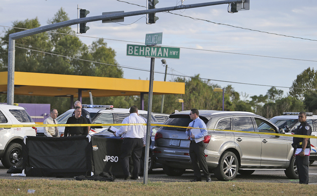 The body of former NFL player Joe McKnight lies between the shooter's vehicle at left and his Audi SUV at right as the Jefferson Parish Sheriff's Office investigates the scene in Terrytown, La., T ...