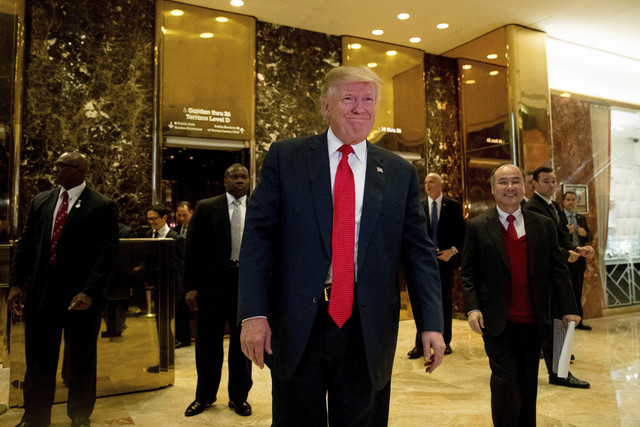 President-elect Donald Trump and SoftBank CEO Masayoshi Son, right, walk into the lobby to speak to members of the media at Trump Tower in New York, Tuesday, Dec. 6, 2016. (Andrew Harnik/AP)