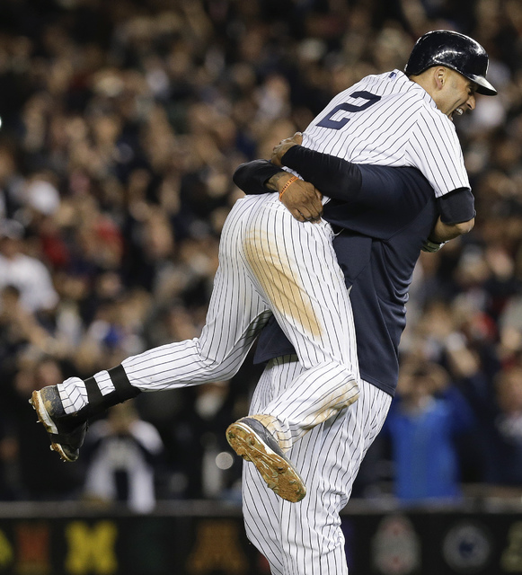 In this Sept. 25, 2014, file photo, New York Yankees' Derek Jeter, left, celebrates with C.C. Sebathia after driving in the game-winning run with a single against the Baltimore Orioles in the nint ...