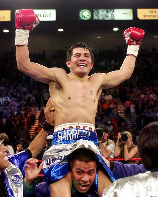 In this April 7, 2001, file photo, Marco Antonio Barrera raises his arms as he parades around the ring after defeating Prince Naseem Hamed to win the IBO featherweight championship at the MGM Gran ...