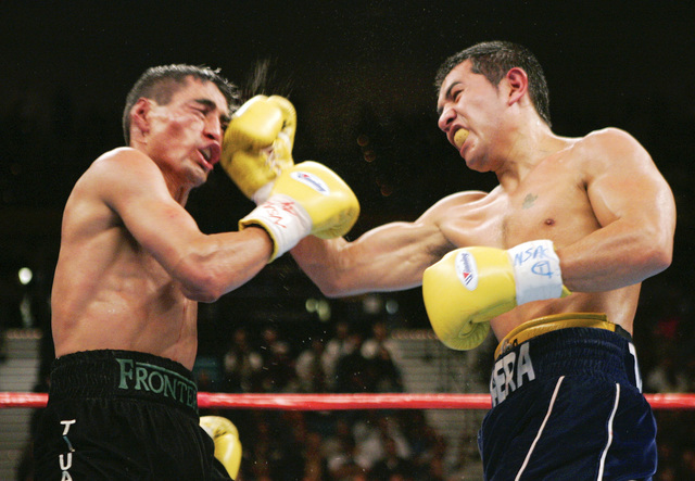 In this Nov. 27, 2004, file photo, compatriots Erik Morales, left, and Marco Antonio Barrera trade punches in the 11th round of their WBC super featherweight title fight at the MGM Grand Garden Ar ...