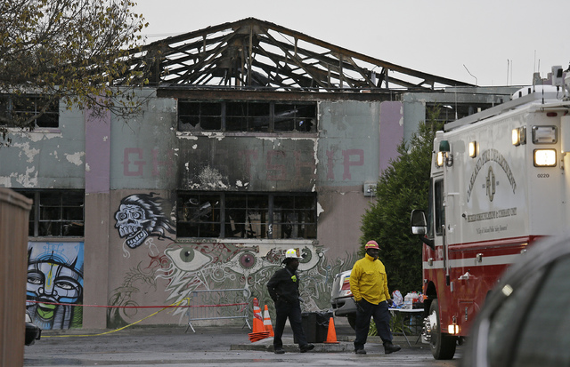 A pair of Oakland fire officials walk past the remains of the Ghost Ship warehouse fire Wednesday, Dec. 7, 2016, in Oakland, Calif. (Eric Risberg/AP)