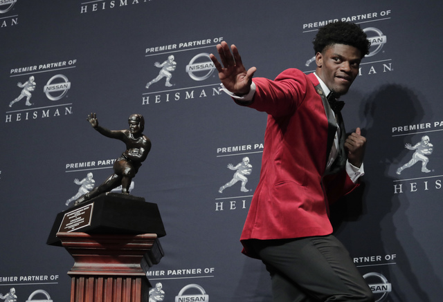 Louisville's Lamar Jackson poses with the Heisman Trophy after winning the award Saturday, Dec. 10, 2016, in New York. (Julie Jacobson/AP)