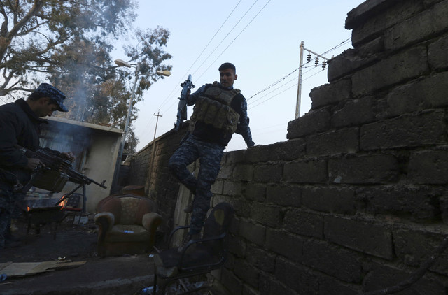 A policeman secures a house as Iraqi federal police forces advance toward the Islamic State militant held city of Mosul, Iraq, Saturday, Dec. 10, 2016. (Hadi Mizban/AP)