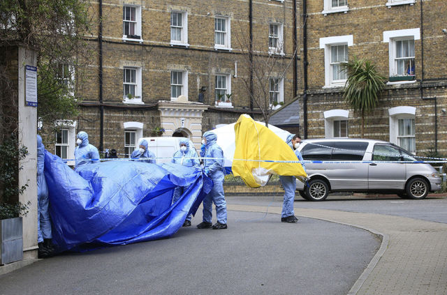 Police forensic officers work at the scene after the remains of PC Gordon Semple, 59, were found at a property in south London, April 8, 2016. (Jonathan Brady/PA via AP, file)