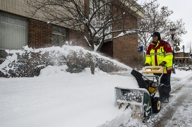 Ryan Wolf clears the sidewalk in front of the Bay City Public Safety Fire Department, in Bay City on Monday, Dec. 12, 2016, as a winter storm pushed eastward. (Jacob Hamilton/The Bay City Times vi ...