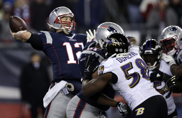 New England Patriots quarterback Tom Brady (12) throws a touchdown pass to Chris Hogan under pressure from Baltimore Ravens linebacker Elvis Dumervil (58) during the fourth quarter of an NFL footb ...