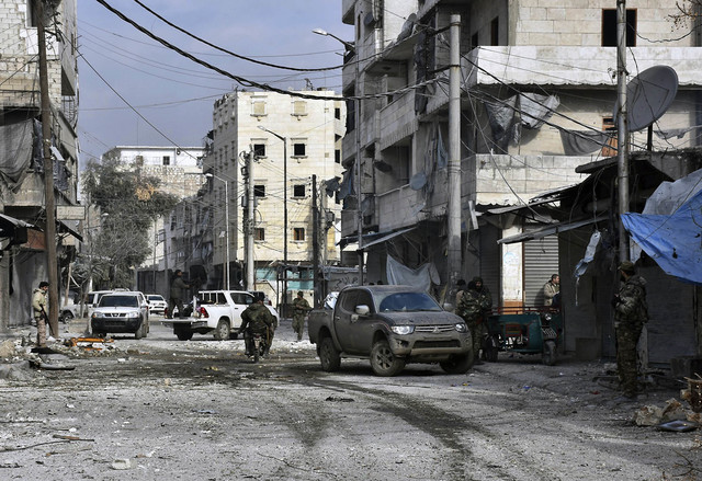 Syrian troops march through the streets of east Aleppo, Syria, Monday, Dec. 12, 2016. Syria's military said Monday it has regained control of 98 percent of eastern Aleppo, as government forces clo ...